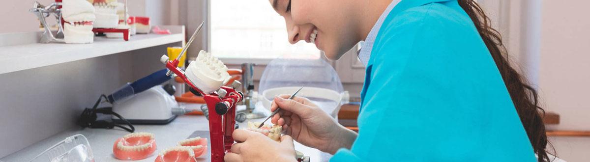 Zahntechnikerin passt Prothese aus dem Dentallabor Zahnwerk in Düsseldorf an die natürliche Zahnfarbe an.